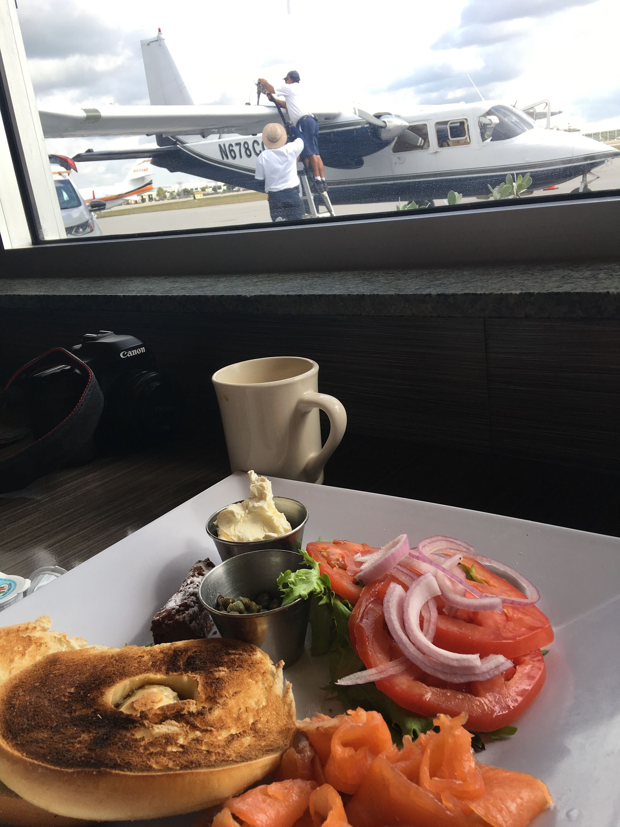 An image of a plate of food while an airplane fuels in the background.