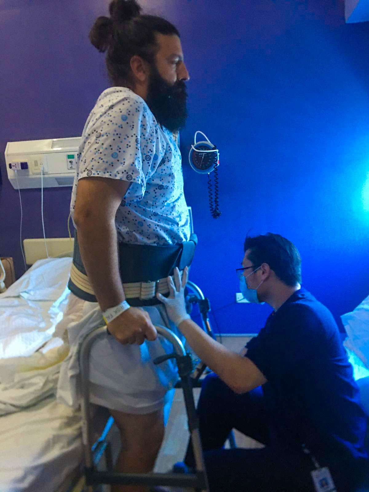 Photo of Chris standing with help from a walker and physical therapist on the first day after his disc removal surgery.